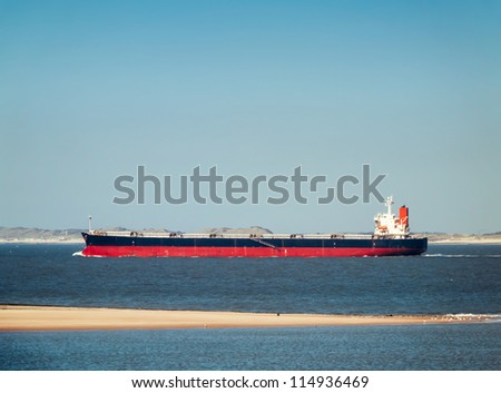 Bulk carrier in north sea with sand bank in foreground - stock photo