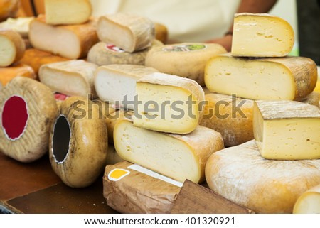Bulks and pieces of different cheese in delicatessen store - stock photo