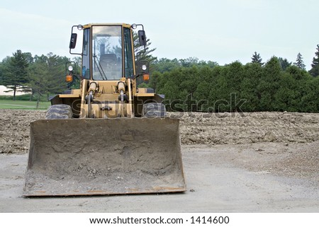 Bull dozer on job site with room at right for text - stock photo