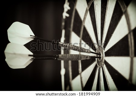 Bull's-Eye ! / Vintage style photo from three darts hit the double Bull's-Eye  - stock photo