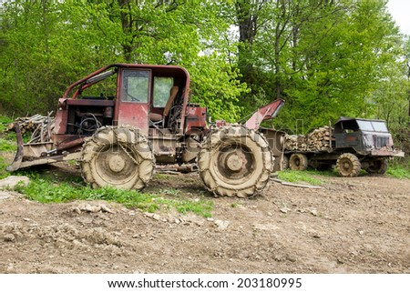 Bulldozer and old truck loaded with logs in a forest