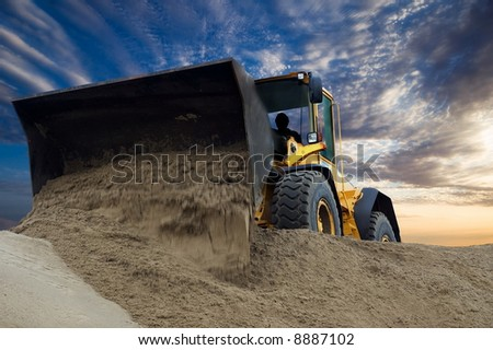 Bulldozer at work with sunset background - stock photo