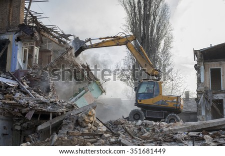 Bulldozer demolishes old buildings - stock photo