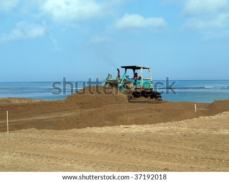 Bulldozer doing construction at beach in Bali picture two - stock photo