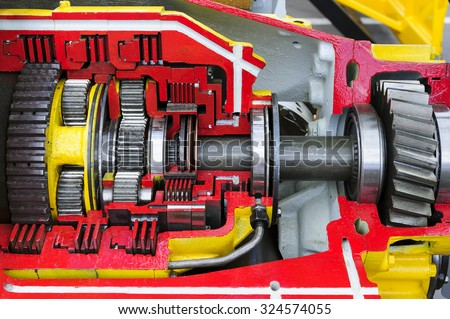 Bulldozer drive gear mechanism cross section, sprockets, bearings, bolts of diesel engine, large construction machine with red and yellow paint coating, heavy industry, detail  - stock photo