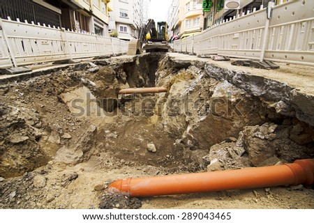 bulldozer excavator  construction vehicle repairing kg sewer pipes in a city street - stock photo