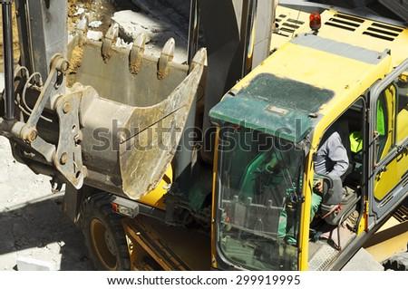bulldozer excavator machine industry picks up debris on city street - stock photo