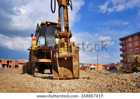 Bulldozer excavator on a construction site against the sky - stock photo