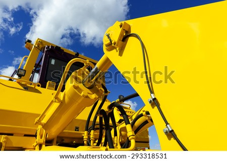 Bulldozer, huge yellow powerful construction machinery with big bucket, focused on hydraulic piston arm, blue sky and white clouds on background - stock photo