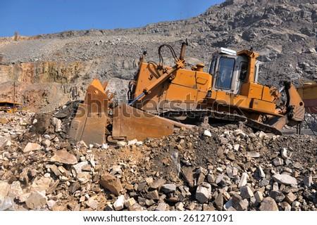 Bulldozer in an open-mine of iron ore - stock photo