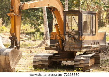 bulldozer in jungle clears trees