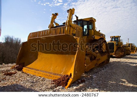 Bulldozer in long line of heavy equipment - stock photo