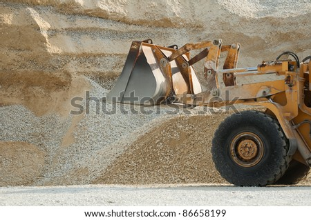 Bulldozer in quarry. Huge pile of limestone and sand - stock photo