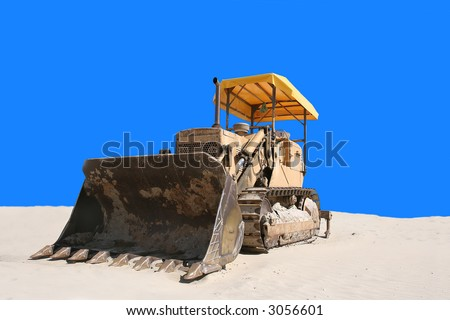 bulldozer in the sand with blue background - stock photo