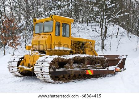 Bulldozer in the snow in winter - stock photo