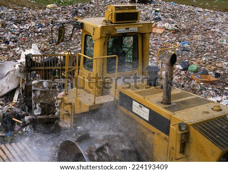 Bulldozer in trash dump - stock photo