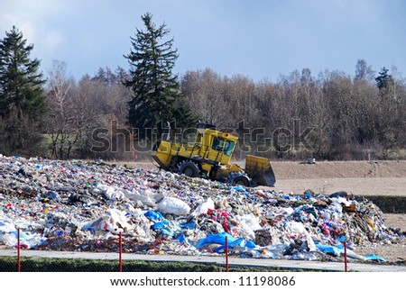 Bulldozer is processing waste in the dump - stock photo