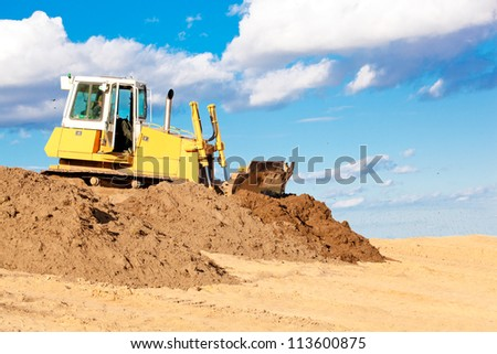Bulldozer machine moving soil at construction site during earth moving works - stock photo
