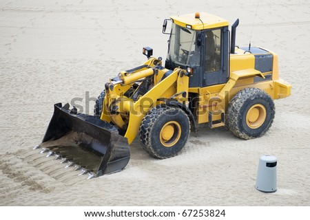 bulldozer - makes cleaning in the sand
