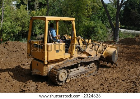 Bulldozer moving dirt with trees in the background - stock photo