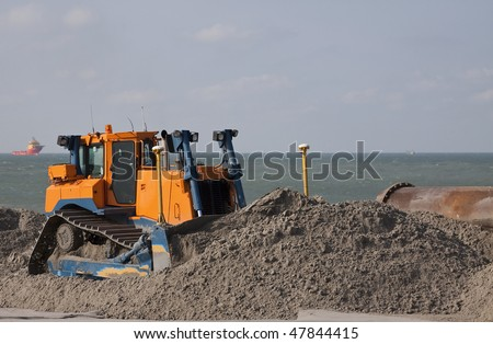 Bulldozer on the beach on a dredging project in holland - stock photo