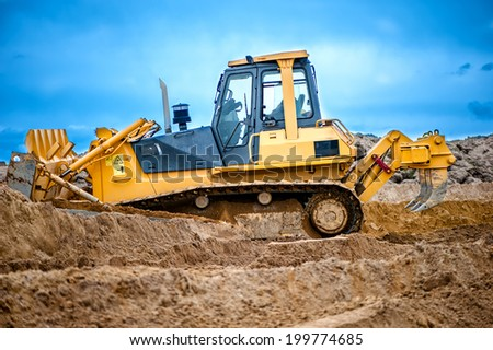 bulldozer or excavator working with soil on construction site of building, road or industrial hall