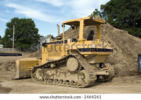 Bulldozer parked in front of a construction project. - stock photo