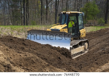 Bulldozer pushing dirt on construction site near a big airport - stock photo