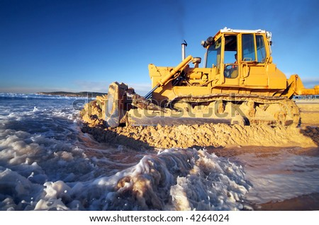 Bulldozer pushing excess sand off beach after big storm surge - stock photo