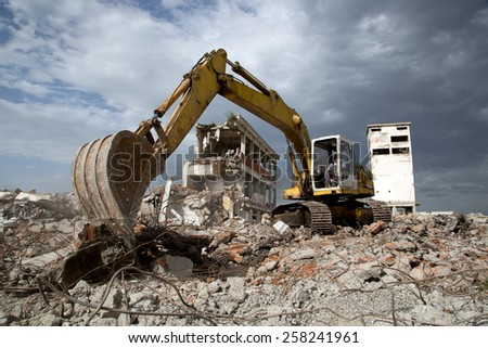 Bulldozer Removes the Debris From Demolition of Old Derelict Buildings - stock photo