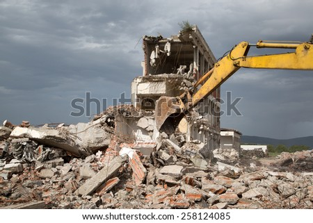Bulldozer Removes the Debris From Demolition of Old Derelict Buildings on the Construction Site - stock photo