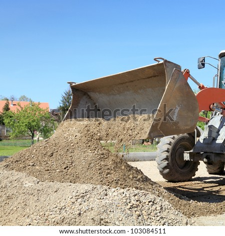 Bulldozer  taking gravel and sand to bucket - stock photo