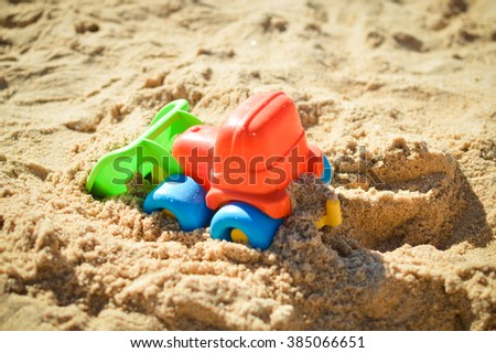 Bulldozer toy on the sandy sunny day outdoors background. Holiday and vacation - stock photo