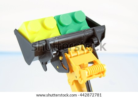 Bulldozer toy with colorful cubes. - stock photo