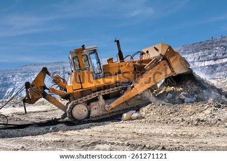 Bulldozer unloading rocks in the open-mine of iron ore - stock photo