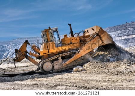 Bulldozer unloading rocks in the open-mine of iron ore - stock photo