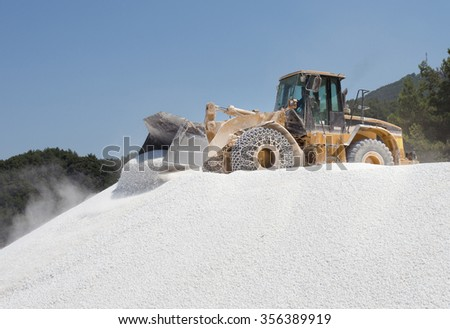 Bulldozer working on the top of huge pile of marble pebble on Thassos in Greece - stock photo