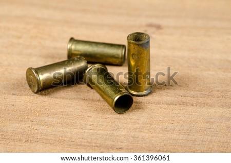 Bullet casings on wooden desk - stock photo