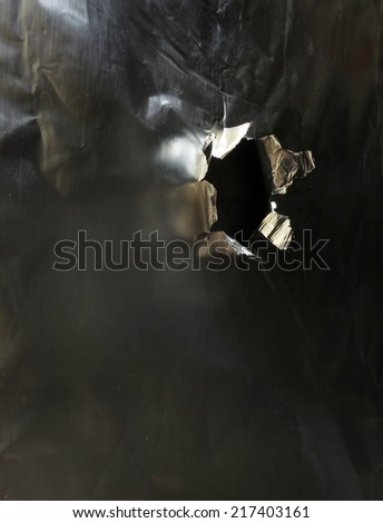 Bullet hole in a piece of metal, side view                               - stock photo