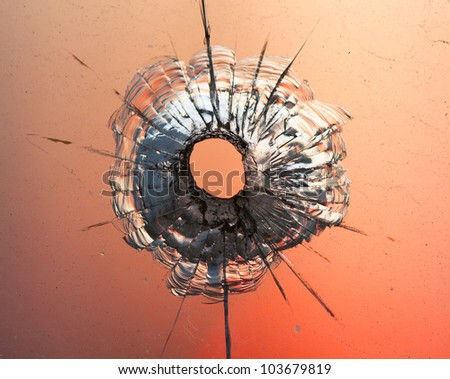 bullet hole in window on the background sunset sky - stock photo