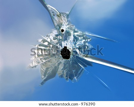 Bullet hole (small calibre) in glass window - stock photo