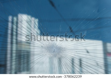 Bullet holes in the window of a shop in city. - stock photo
