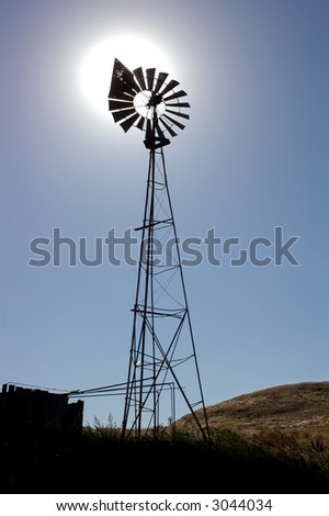 Bullet Ridden Ranch Windmill Silhouette with Blazing Sun Behind