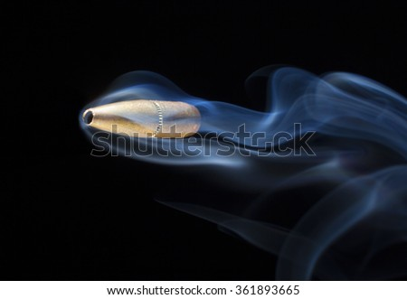 Bullet with a copper coating that with smoke behind on a black background - stock photo
