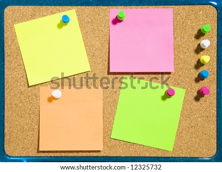 bulletin board and multi colored stickies attached with push pins. Copy space
