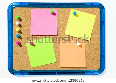 bulletin board and multi colored stickies attached with push pins. Isolated on white and copy space