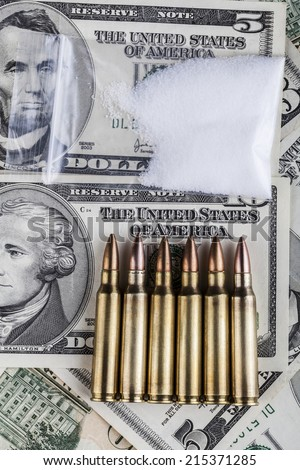 Bullets on dollar banknotes with bag of white drug powder on black background - stock photo