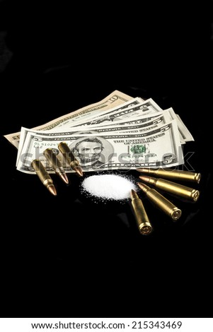 bullets on dollar banknotes with white drug powder on black background - stock photo