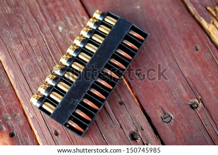 Bullets on wooden table - stock photo
