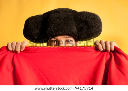 Bullfighter afraid with big montera hidden behind cape humor spanish colors